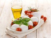 Buffalo mozzarella with basil and tomatoes — Stock Photo