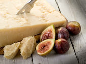 Parmesan cheese over cutting board and figs — Stock Photo