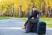 Businesswoman sitting on a bags — Stock Photo