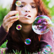 Stock Photo: Young womblowing bubbles