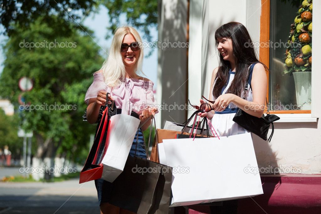 Two young women with shopping bags on the steps — Stock Photo #6217852