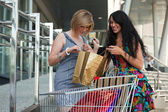 Two young women with shopping cart — Stock Photo