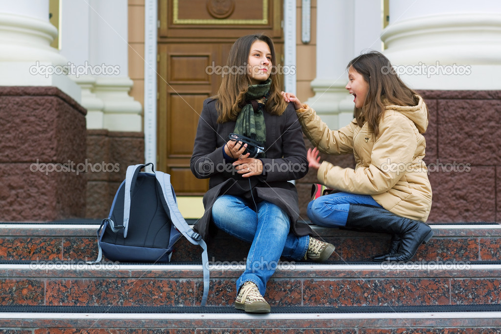 Two young teenage students sitting on the stairs of a high school. — Stock Photo #6233055