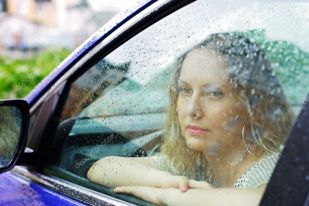 Sad young woman looking through window with a rain drops. — Stock Photo #6233057