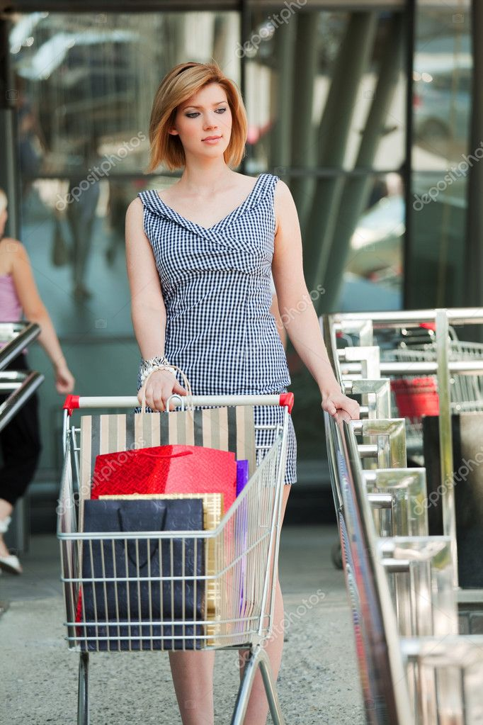 Young woman with shopping cart on the store stairs. — Stock Photo #6233461