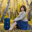 Royalty-Free Stock Photo: Thoughtful woman with a suitcase
