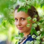 Beautiful woman among blossoming trees — Stock Photo #6258591