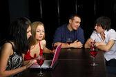 Jóvenes amigos con el portátil en un bar de noche — Foto de Stock