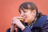 Teenage girl eating a burger — Stock Photo