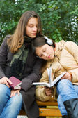 Two young girls reading in the park — Stock Photo