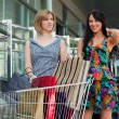 Two young women with shopping carts — 图库照片