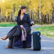 Businesswoman sitting on a bags — Stock Photo #6303937