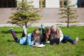 Teenage schoolmeisjes liggend op een gras — Stockfoto