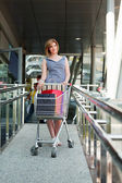 Young woman with shopping cart — Stockfoto