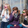 Teenage girls relaxing against a city fountain — Stock Photo