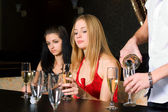 Two young women in a night bar — Stock Photo
