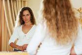женщина смотрит в зеркало — Стоковое фото