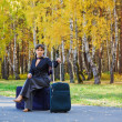 Stock Photo: Thoughtful woman with a luggage