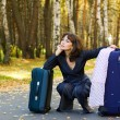 Thoughtful woman with a luggage — Stock Photo