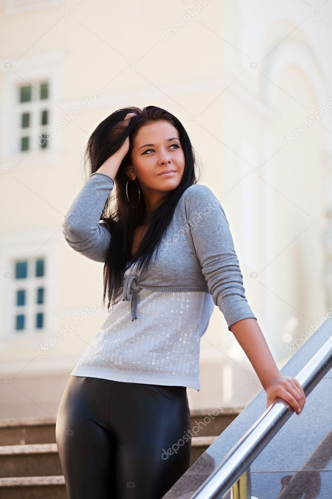 Beautiful young brunette leaning on the handrail. — Stock Photo #6344397