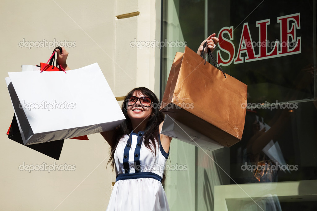 Young woman with shopping bags against of store entrance. — Stock Photo #6345339