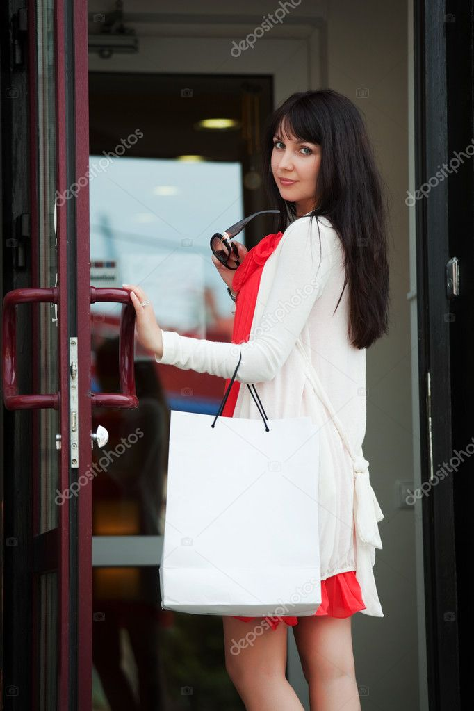 Young woman with shopping bags against of store entrance.  Stock Photo #6345344
