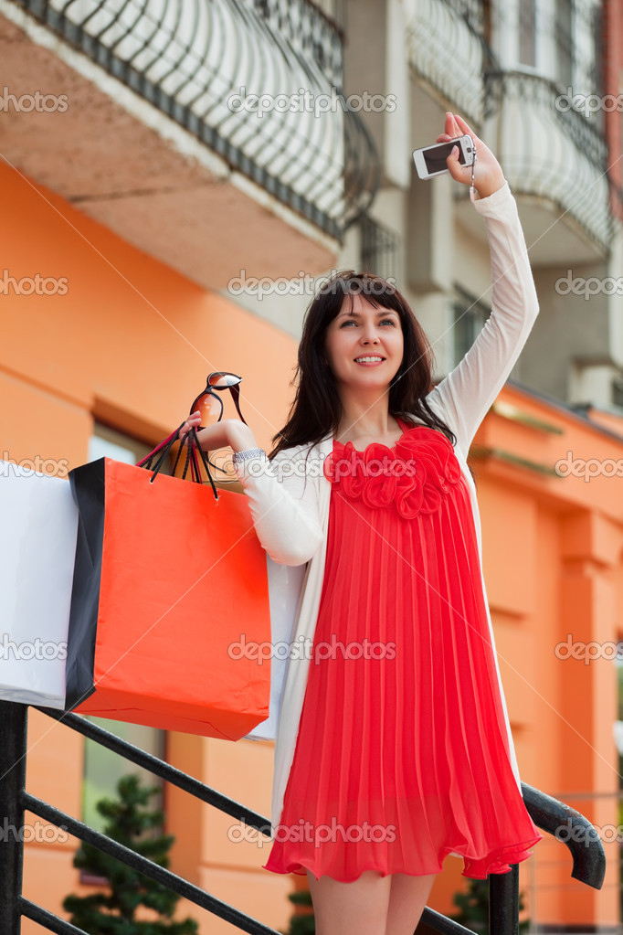 Happy young woman with a mobile phone on the shop stairs.  Stock Photo #6345372