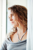 Sad woman looking through a window — Stock Photo