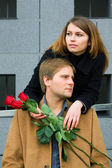 Young couple with a red roses — Stock Photo