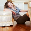 Stock Photo: Beautiful womleaning on ottoman