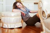 Beautiful woman leaning on the ottoman — Stock Photo