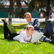 Young business with laptop in a city park - Stock Photo