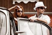 Ungt par med en retro bil — Stockfoto