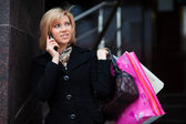 Young blond shopper on the phone — Stock Photo