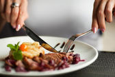 Female hands with a dinner at restaurant. — Stock Photo