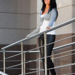 Beautiful woman leaning on the handrail — Stock Photo