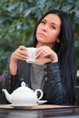 Young woman at sidewalk cafe — Stock Photo