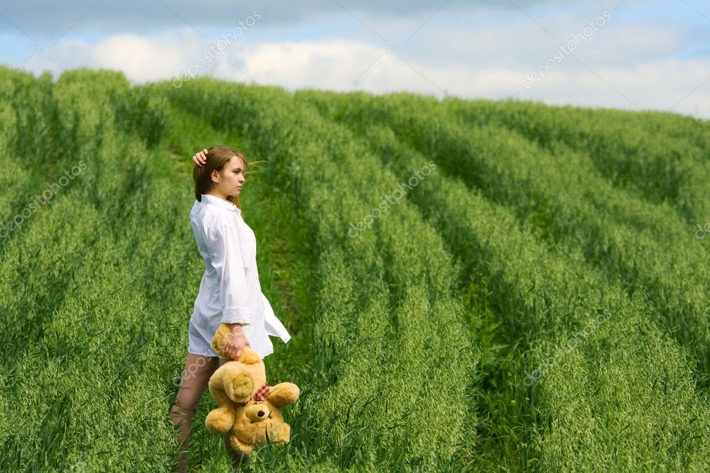 Sad young woman with teddy bear on nature.  Stock Photo #6477541