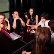 Young friends with laptop in a bar — Stock Photo