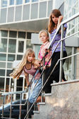 Group of teenage girls on a shop steps — Stock Photo
