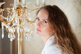 Beautiful woman against a chandelier — Stock Photo