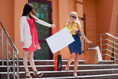 Two young women with shopping bags on the steps — Stock Photo