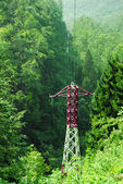 High voltage electric poles trough the mountains — Stock Photo