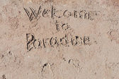 "Inscription ""Welcome to Paradise"" on beach. — Stock Photo"