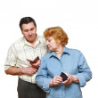 Stock Photo: Old married couple look at pension ID's.