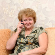 Senior lady speaks by a mobile phone. - Zdjęcie stockowe