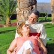 Mature couple lying in embrace near palm-tree. — Stock Photo #6514115