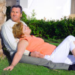 Mature couple lying in embrace near palm-tree. - Stock Photo
