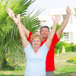 Elderly couple near the palm-tree. — Stock Photo