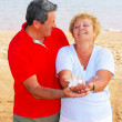 Elderly couple on the coast ,holding corals. — Stock Photo
